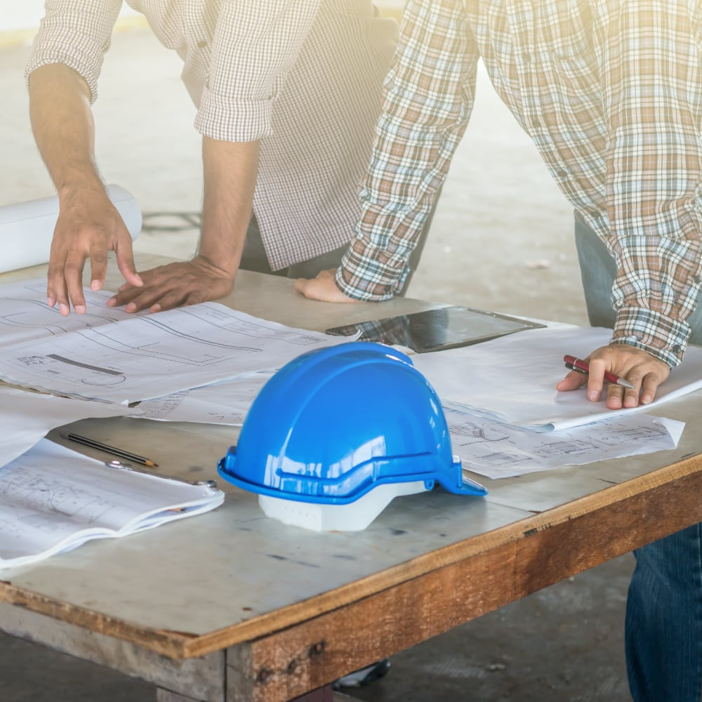 Two men looking at blueprints on a construction site