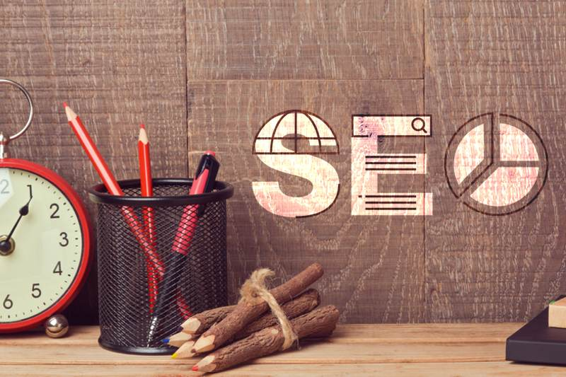 Letters SEO on wood wall behind work desk