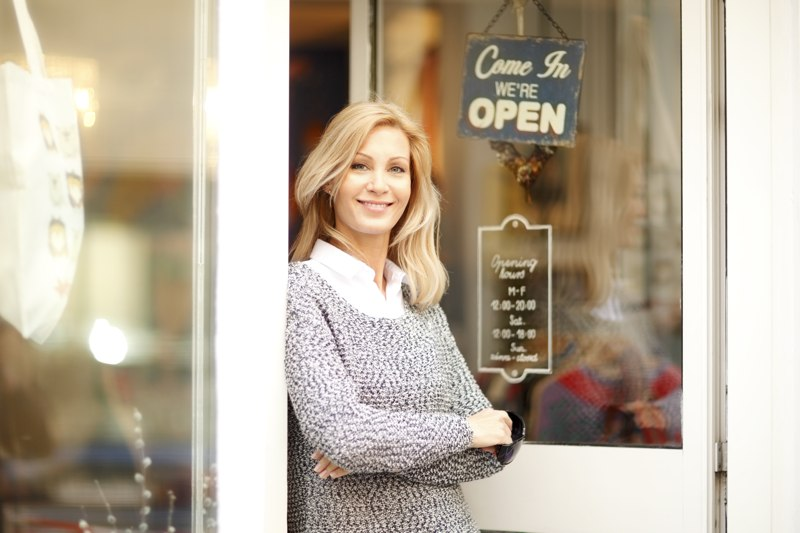 A small business owner stands in a door, wondering how much does a small business website cost?