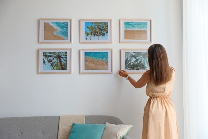woman hanging up tropical photos on wall in staged home