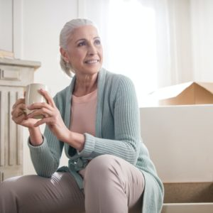 senior woman drinking coffee surrounded by moving boxes