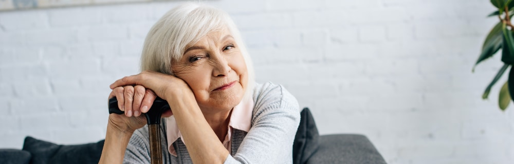 senior woman leaning head and hands on cane