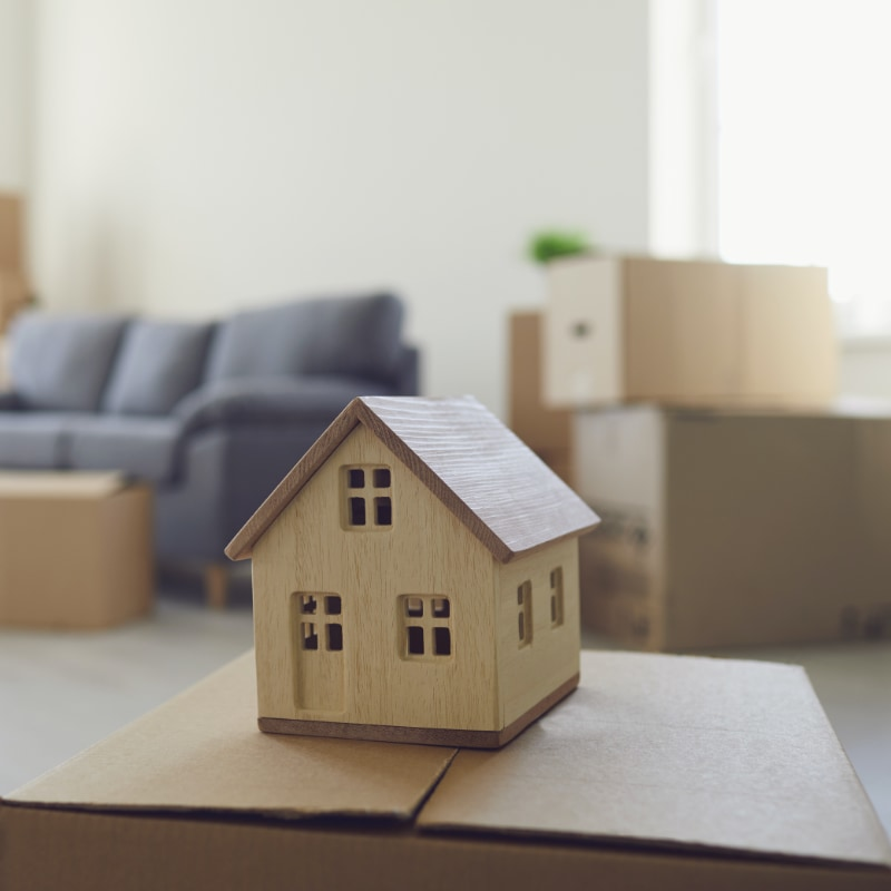 little wooden house decoration sitting on moving box