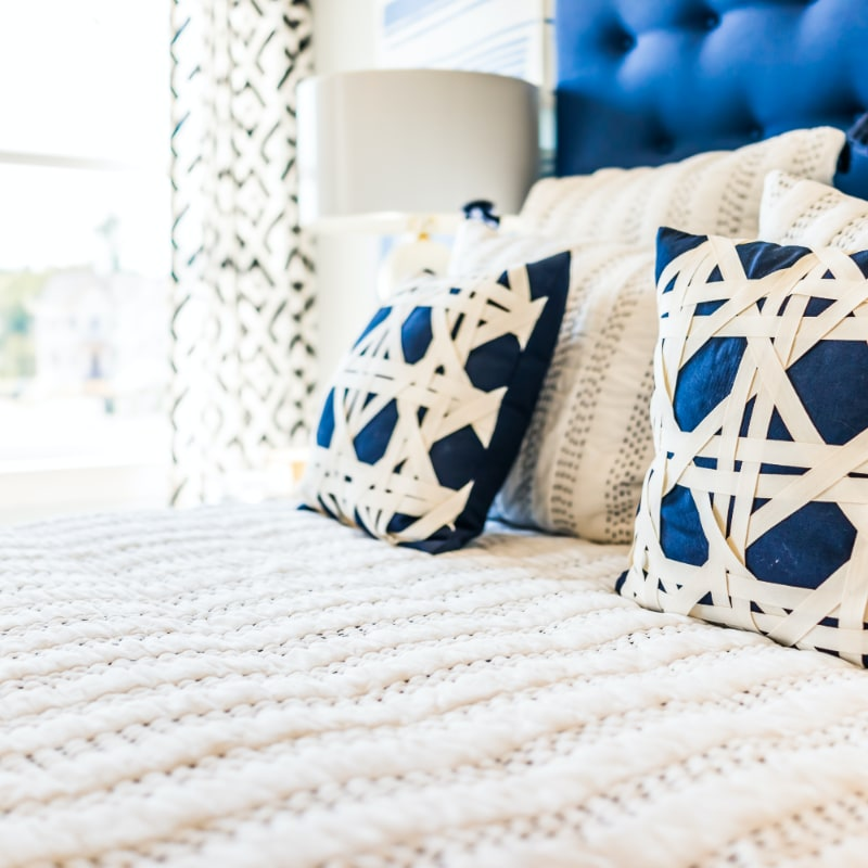 perfectly staged white bed with blue and white decorative pillows