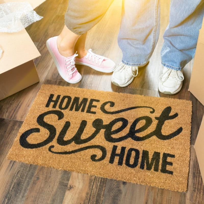 feet of couple in tennis shoes next to home sweet home welcome mat