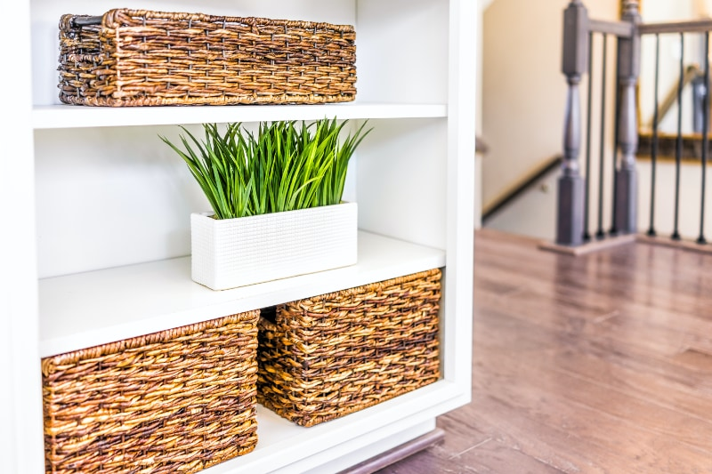 wicker baskets and plant staged on shelf in home