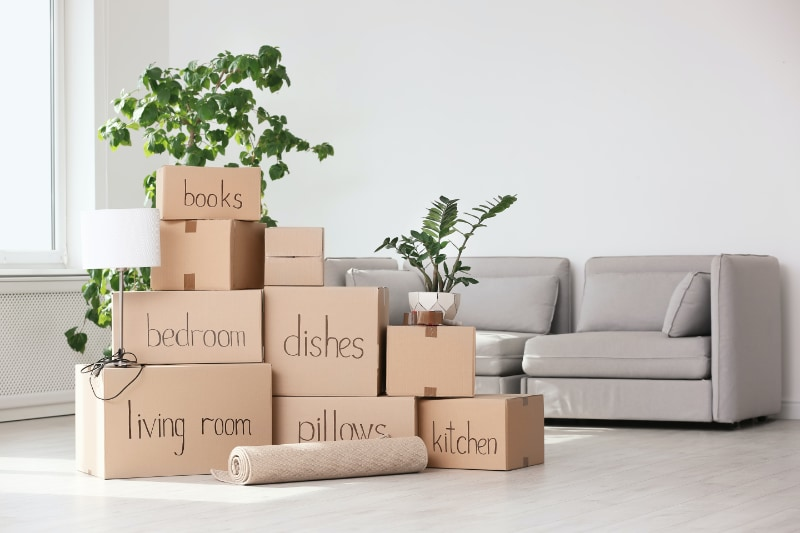 moving boxes labeled and stacked in living room near couch
