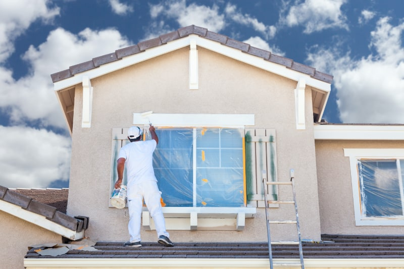 Exterior house painter working on window trim.