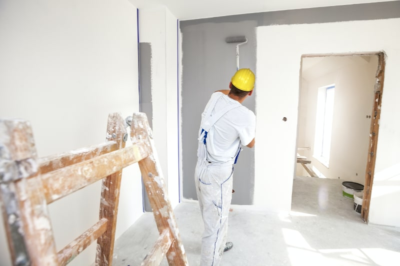 Home interior painter rolling paint on wall in bedroom.