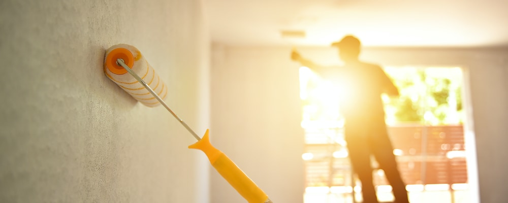 Professional painting company rolling paint on home interior walls.