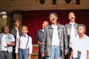 young boys singing together in performance