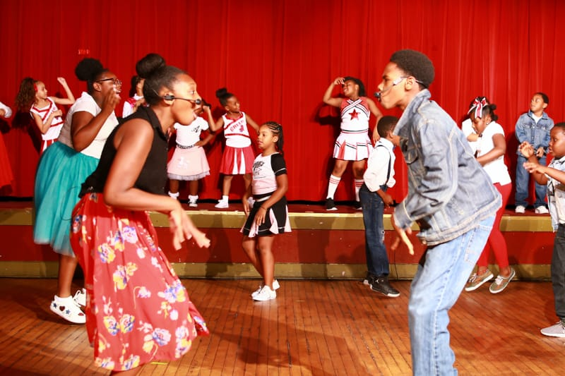 teenage boy and girl facing each other singing with kids dancing in background