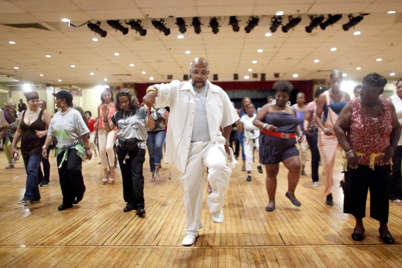 man in white outfit leading group of adults dancing