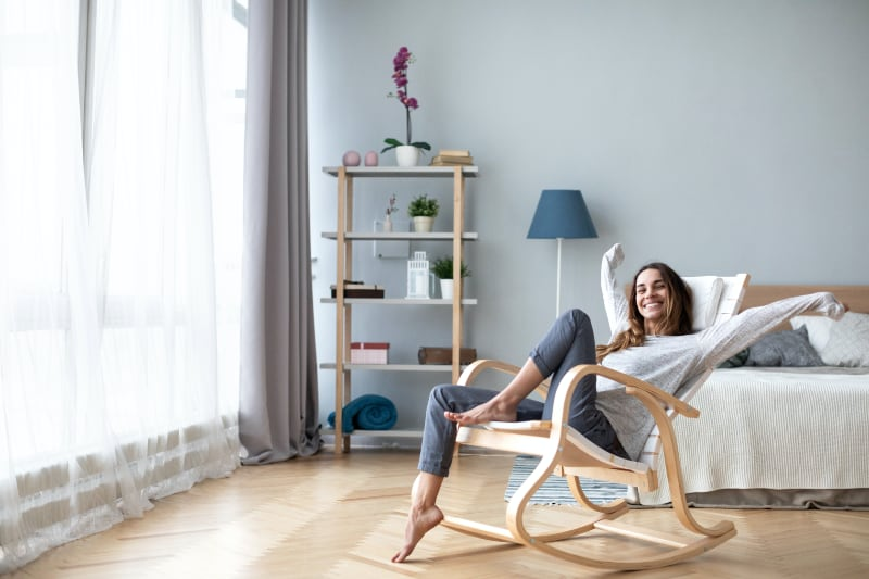 Happy woman rocking in chair in her new remodeled home.