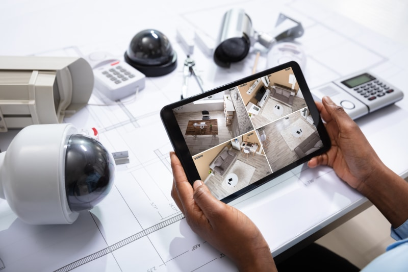 cctv equipment spread out over blueprints and tablet showing camera scenes