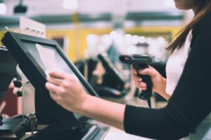 shop cashier scanning receipt at POS display