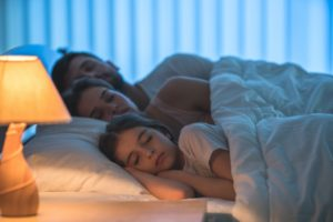 family asleep in bed with lamp light on