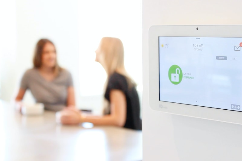 two women talking at kitchen table with security smart home panel on wall