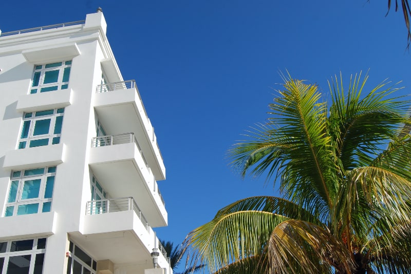 looking up at condo complex balconies with palm tree in foreground