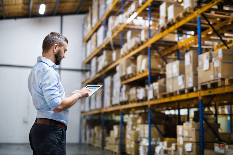 warehouse worker looking at tablet in front of tall shelves of boxes