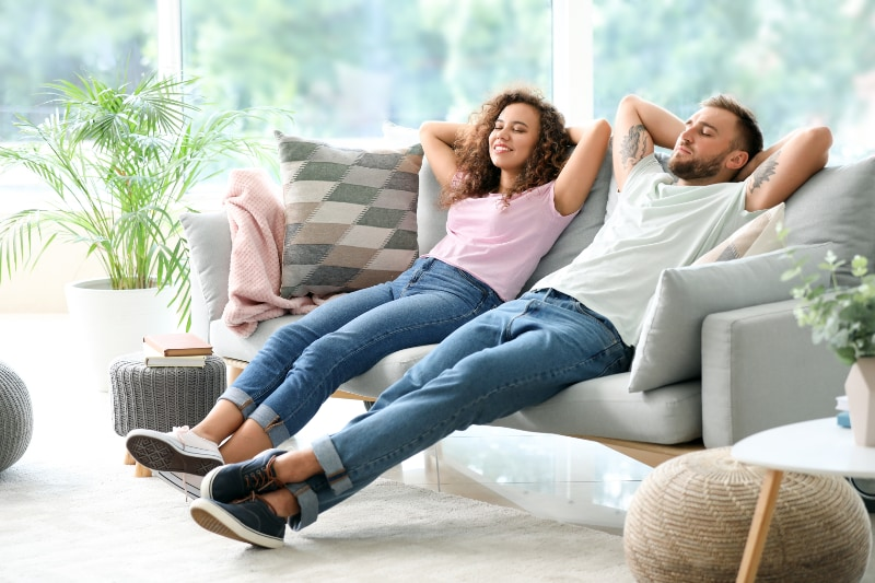 couple in home relaxing on couch in the comfort of air conditioning
