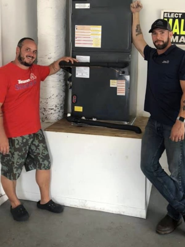 Owner Oaki standing with happy client next to new HVAC unit