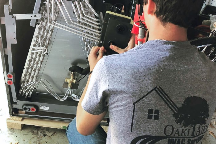 Oaki-Aire AC expert working on unit maintenance