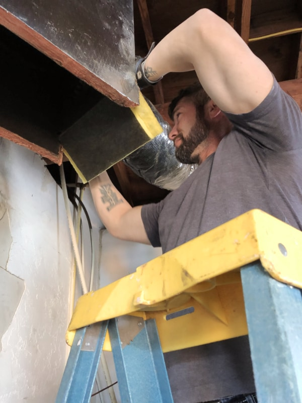 Owner Oaki standing on a ladder and working on HVAC ductwork