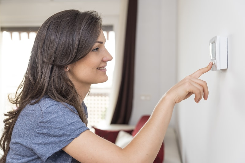 smiling woman turning up heat on a thermostat attached to the wall