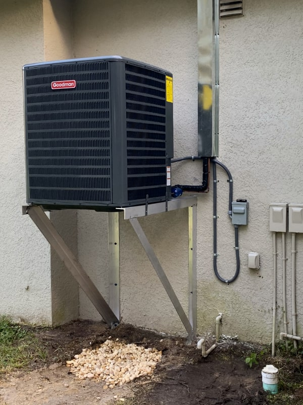 Goodman brand air conditioner unit elevated off ground with metal framework