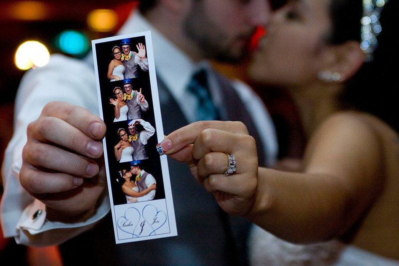 Couple kissing behind their photo booth image print out.