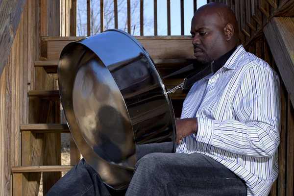 A steel pan drummer playing softly on a staircase.