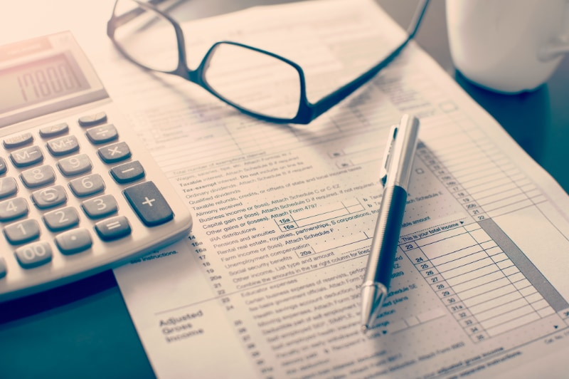 Tax documents sitting on desk with calculator, glasses, and a pen.